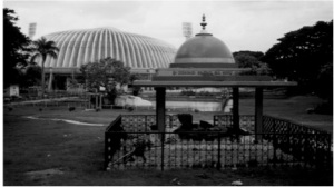 small shrine in foreground with park and stadium in background