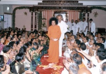 Sathya Sai Baba leads a small procession of men as devotees seated on either side offer devotion