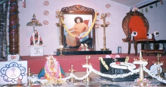 "Inside the Sai center in Indiranagar. The altar area contains a photograph of Sathya Sai Baba placed for worship, a chair signifying his ""presence,"" and a small image of Shirdi Sai Baba (Sathya Sai Baba is believed by his devotees to be a reincarnation of this Maharashtrian holyman)."