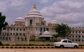 Sathya Sai Institute of Higher Medical Sciences building with fence and Ambassador car parked in front